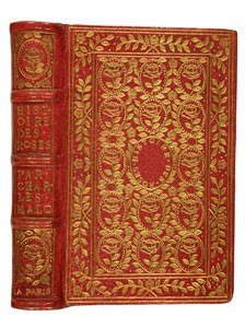 An old fashioned bound book with red cover and fancy gold leaf lettering and design