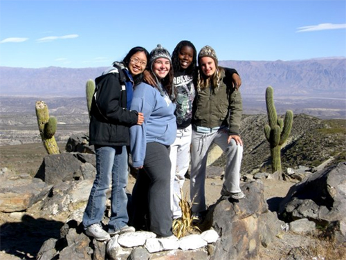 Four girls posing for a picture against the background of desert and mountains