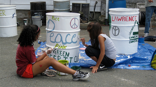 Two girls sitting on the ground painting colorful messages on metal barrels