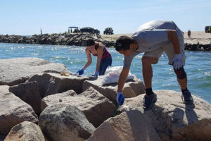 Volunteers picking trash up from along the waterside